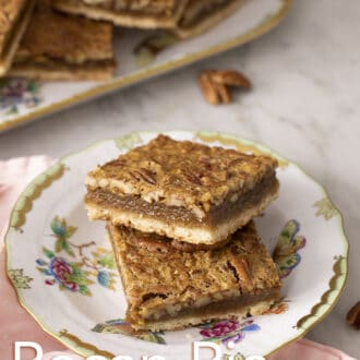 pecan pie bars stacked on a floral plate