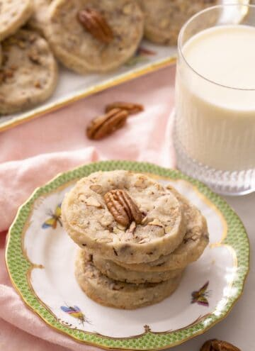 A stack of pecan sandies on a plate next to a glass of milk.
