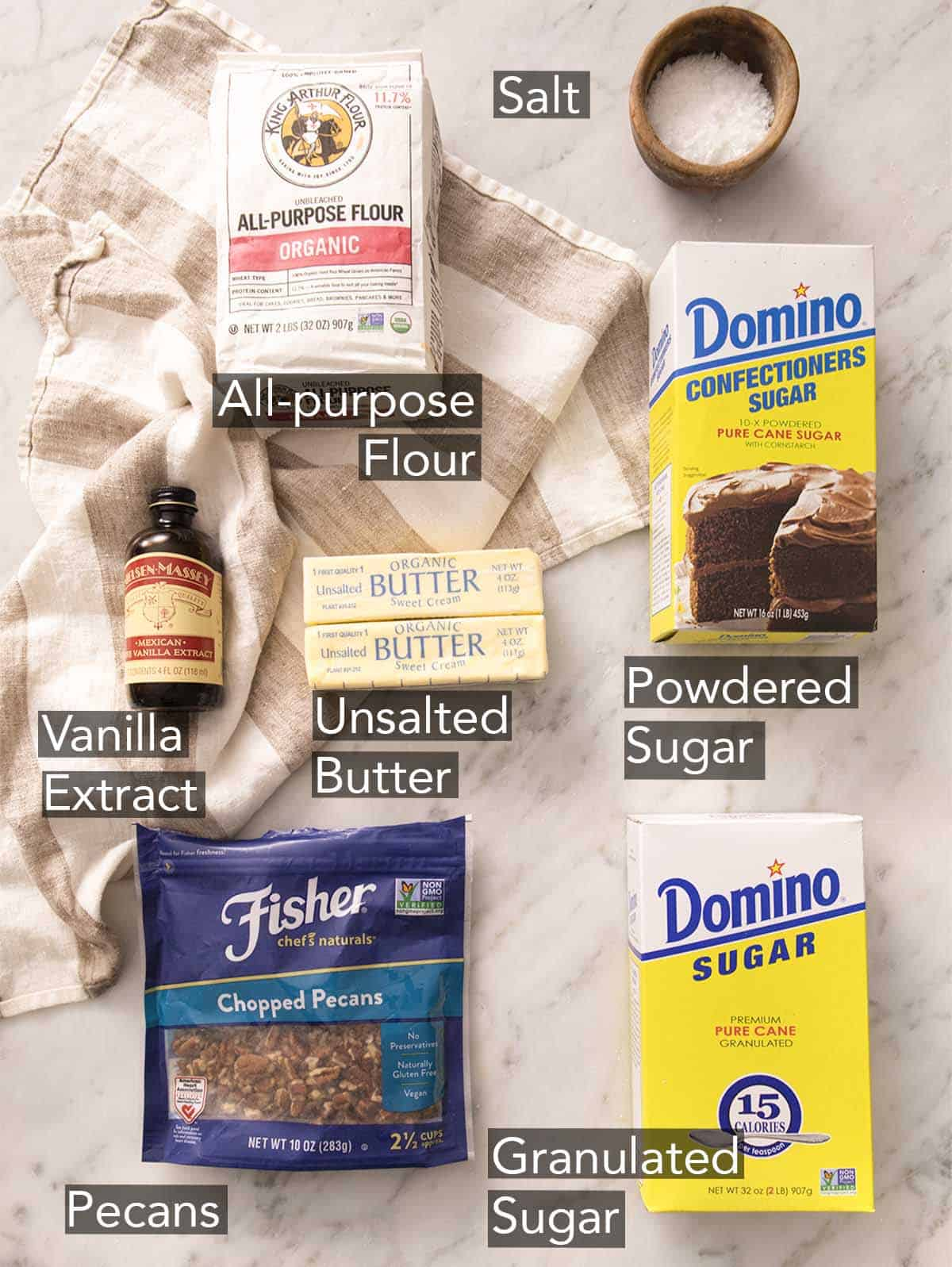 Ingredients to make pecan sandies on a marble counter.