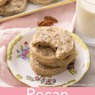 pecan sandies stacked on a floral plate with a glass of milk
