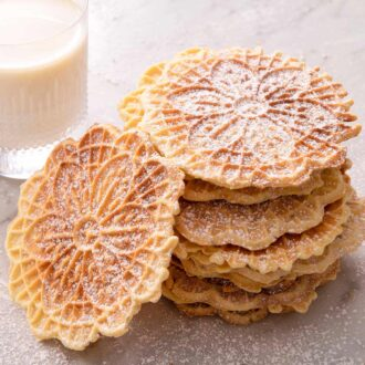 A close up of a stack of pizzelle cookies with a glass of milk in the background