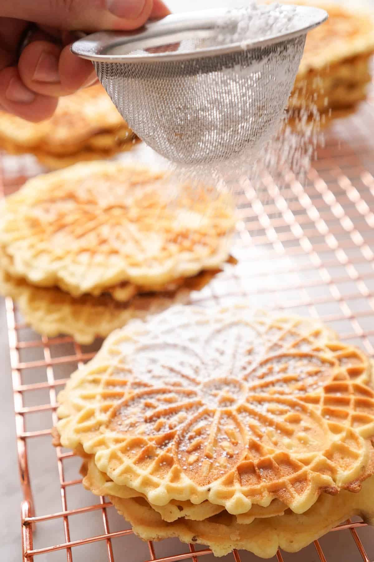 powdered sugar getting dusted over pizzelle cookies