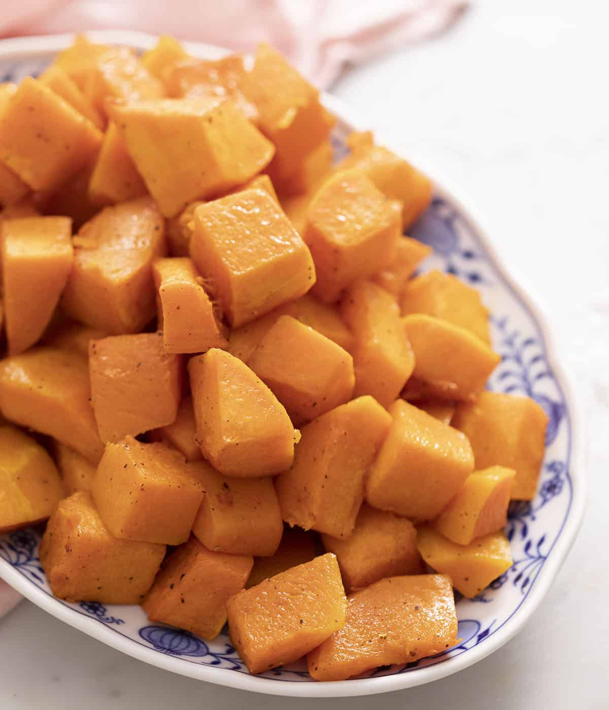Roasted butternut squash in a blue and white serving dish.