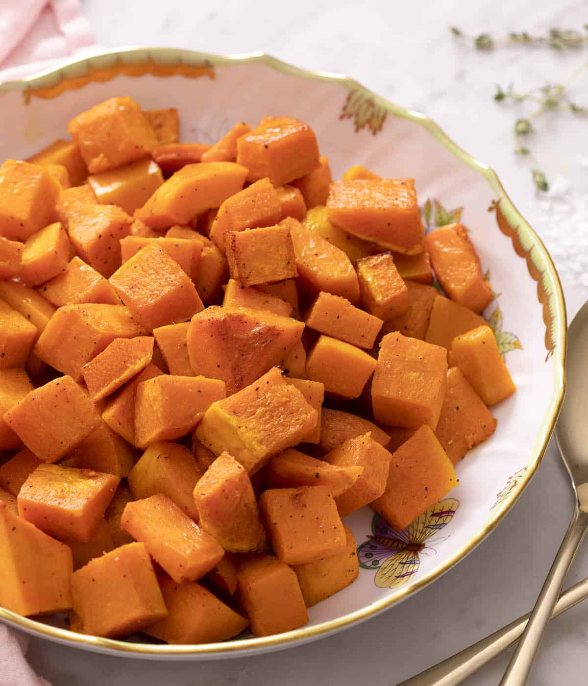 A round porcelain serving bowl filled with roasted butternut squash.