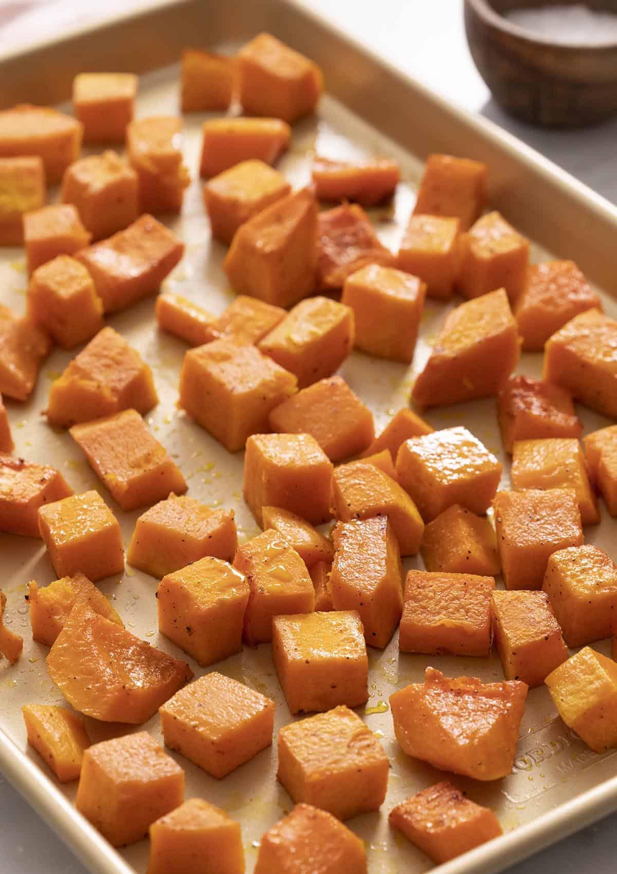 Roasted butternut squash pieces on a golden baking sheet.