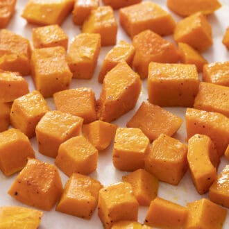 Cubes of roasted butternut squash on a piece of white parchment paper.