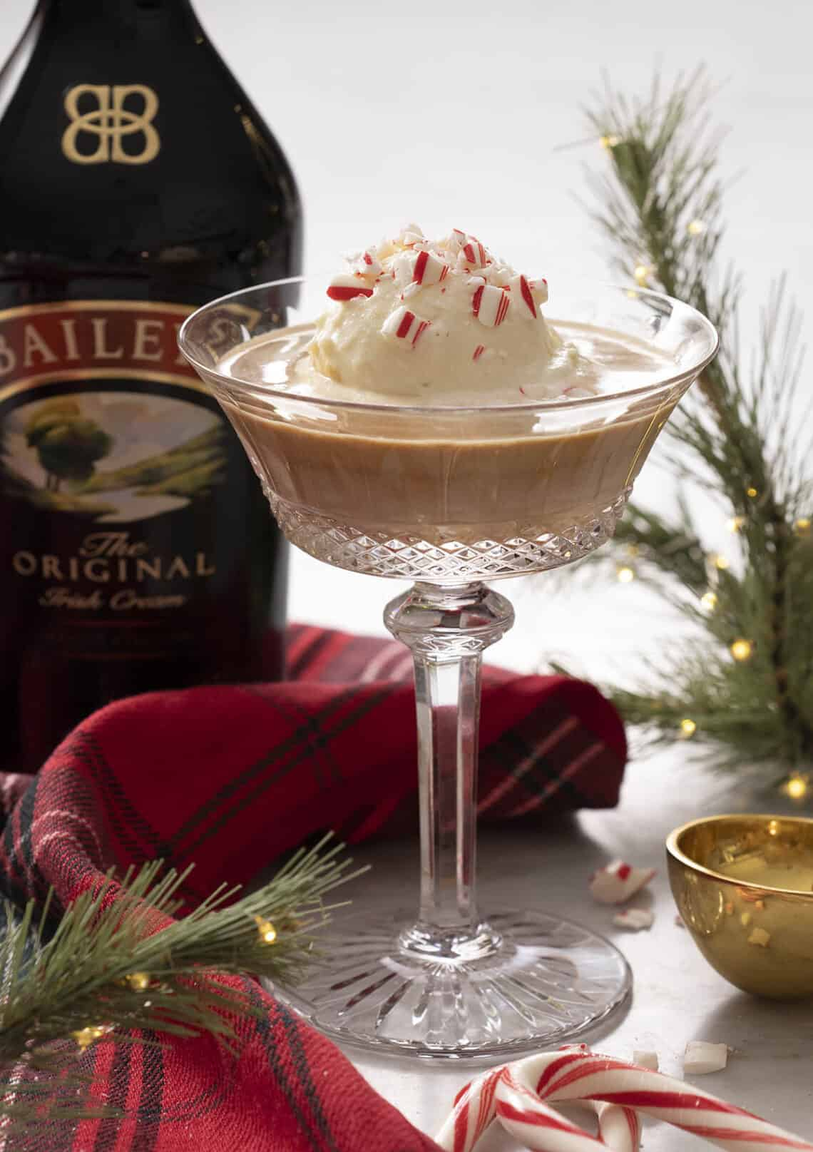 A Baileys affogato in a crystal glass with crushed candy cane on top.