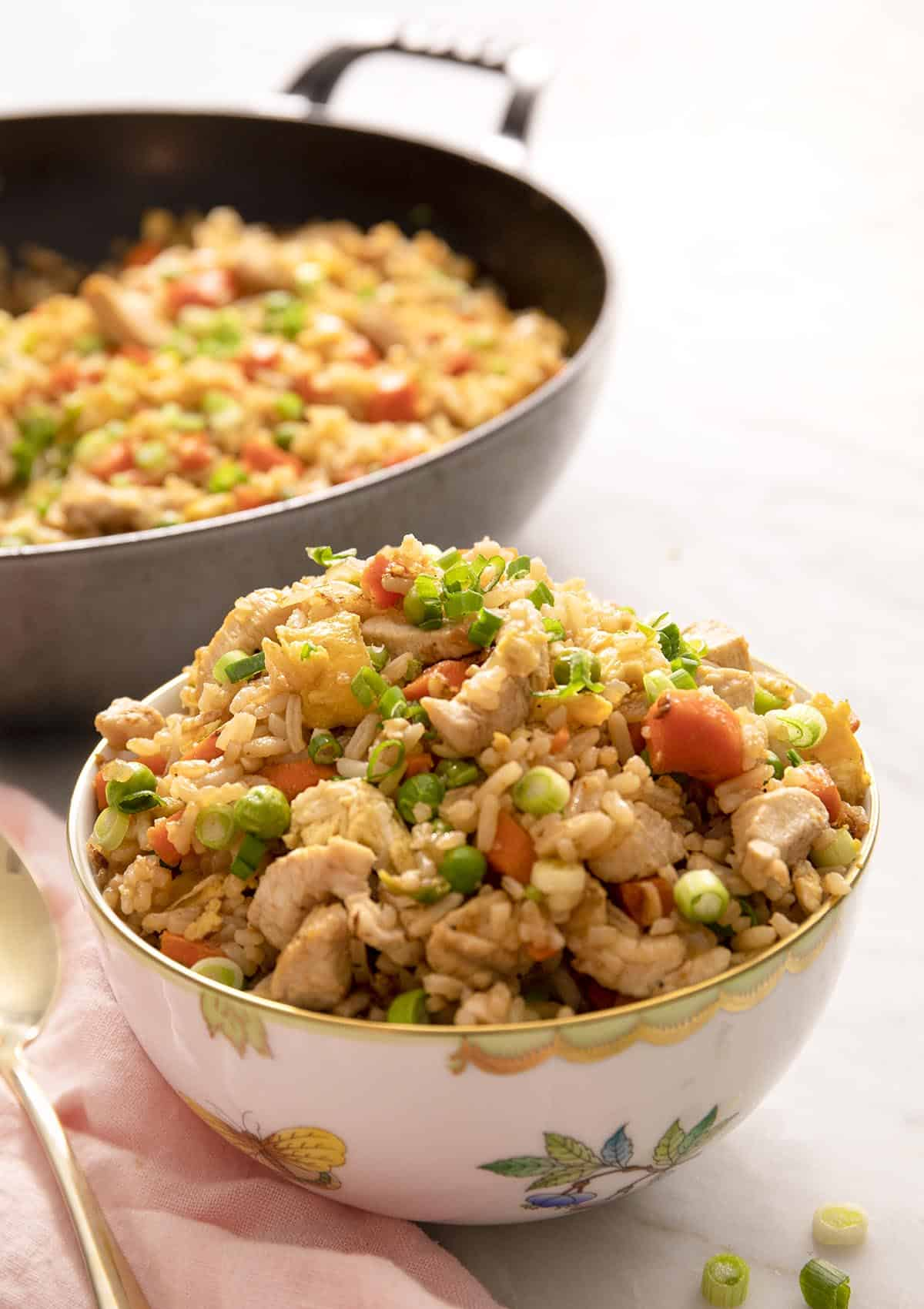 Chicken fried rice in a white bowl with a skillet behind it
