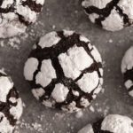 Chocolate crinkle cookies covered in powdered sugar on a grey surface.