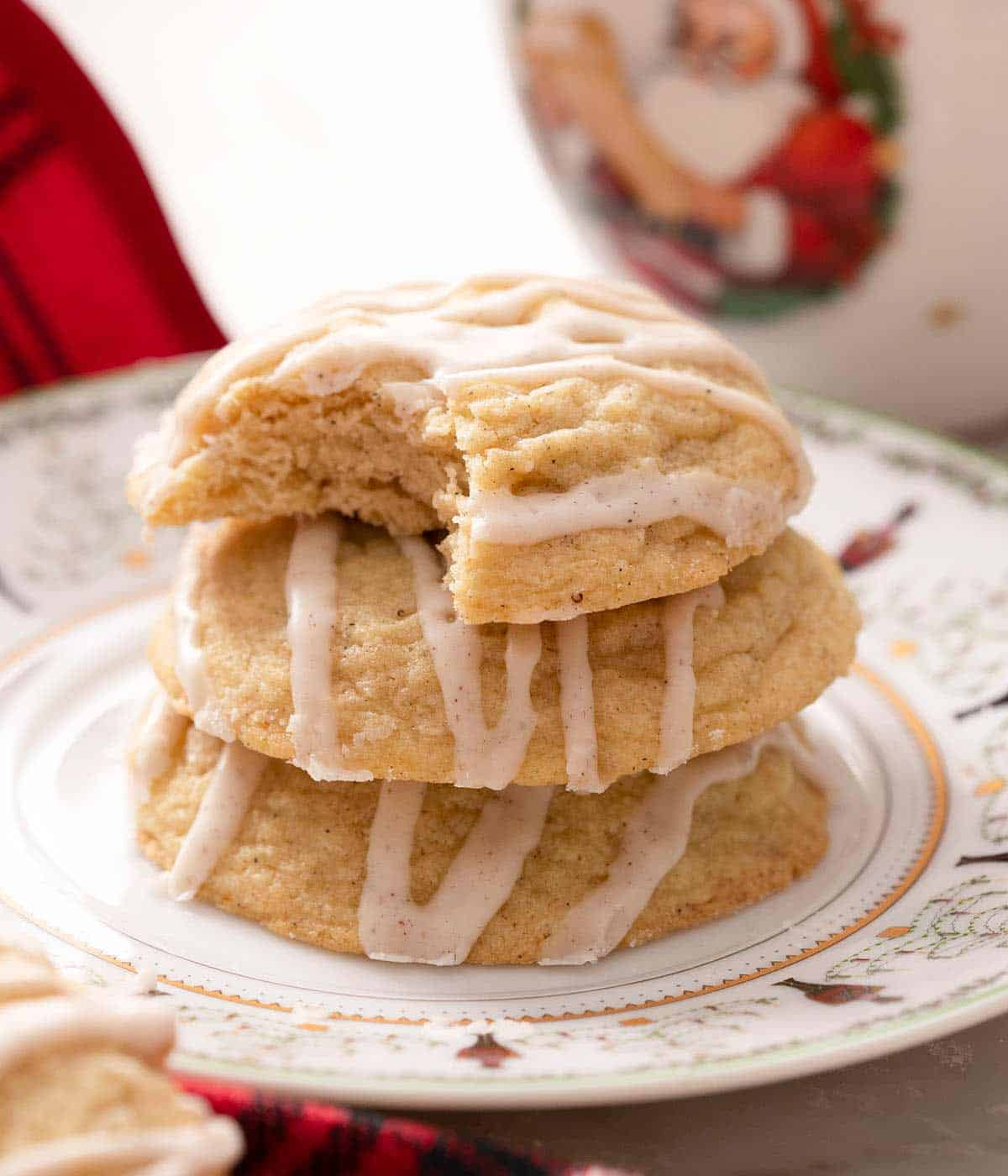 A photo of eggnog cookies stacked on top of each other and one with a bite out