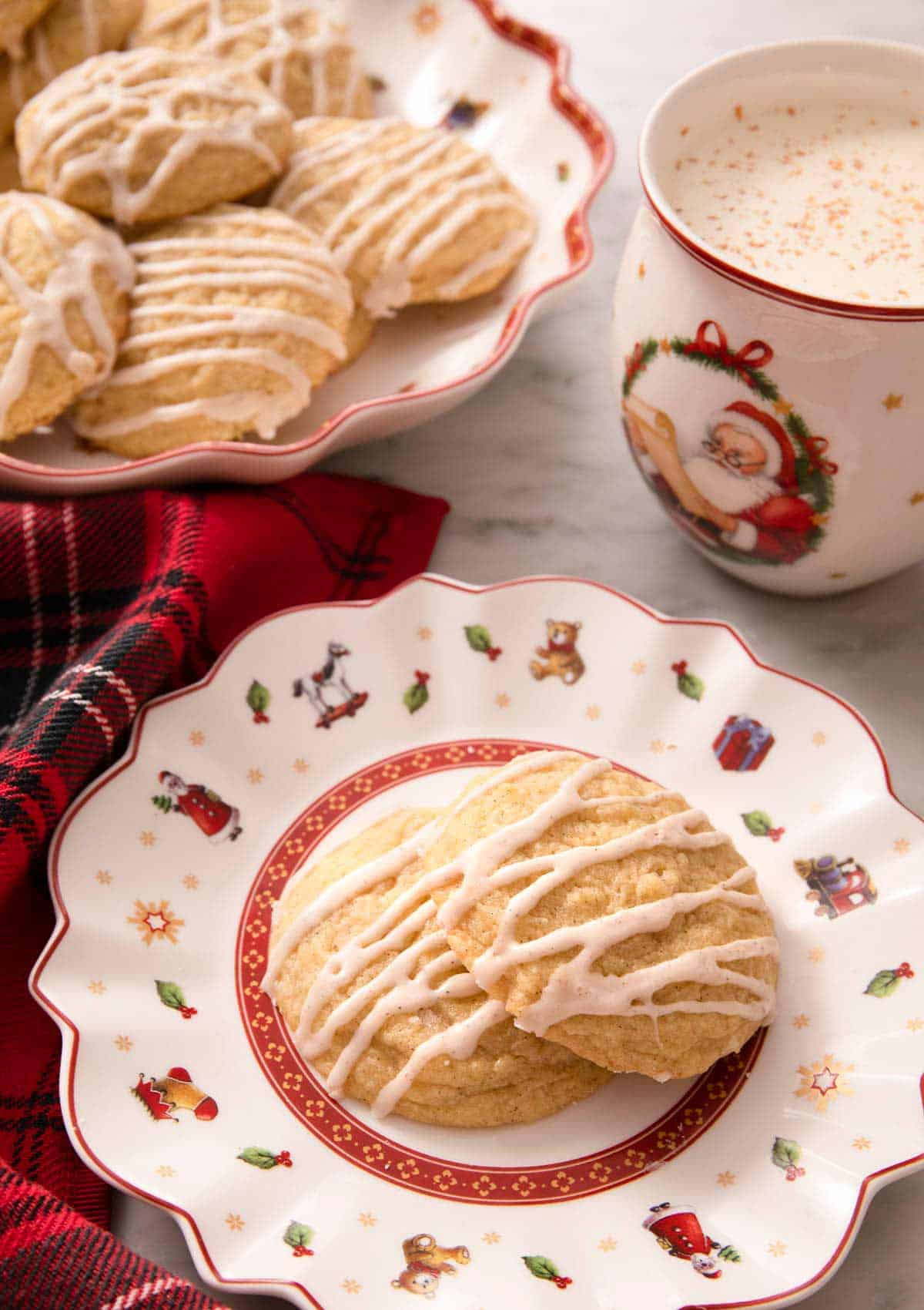 Eggnog cookies on a plate with a mug of hot cocoa behind it