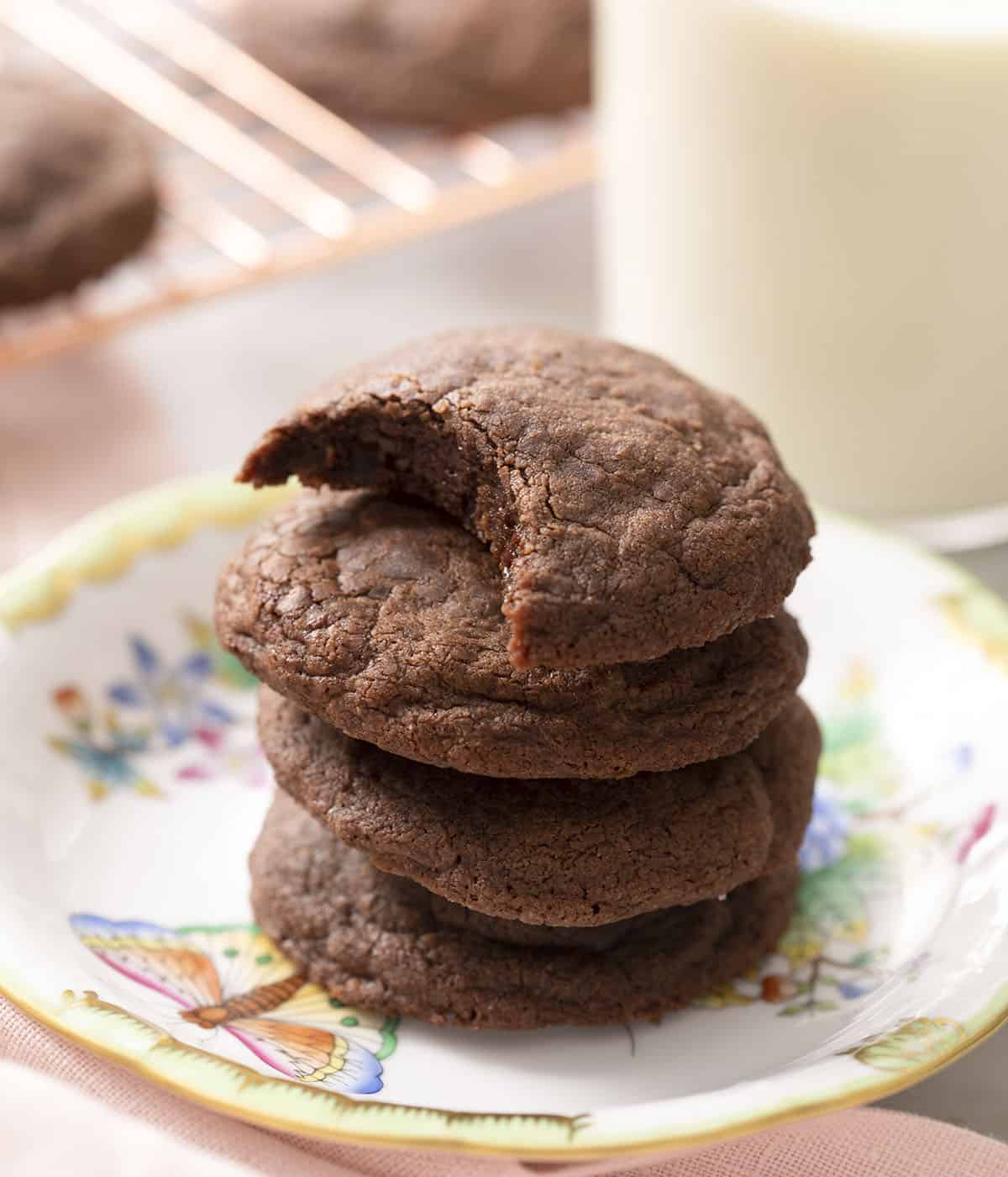A stack of nutella cookies on a plate one with a bite out