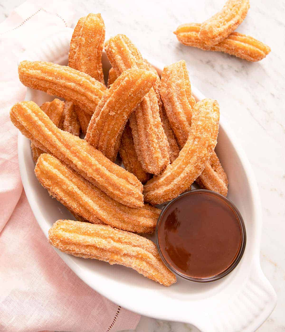 An overhead shot of churros on a serving plate