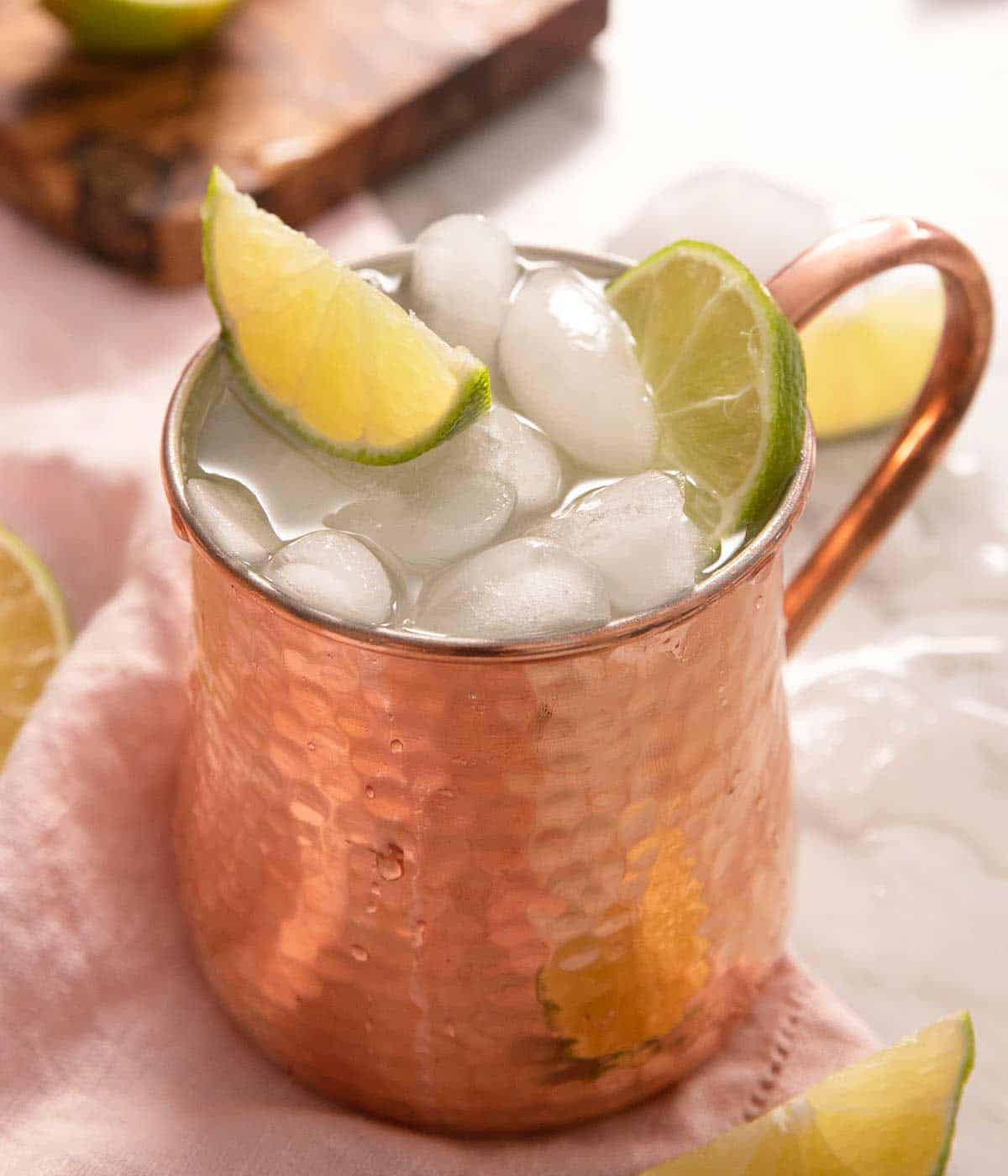 A close up of a Moscow Mule cocktail topped with lime wedges