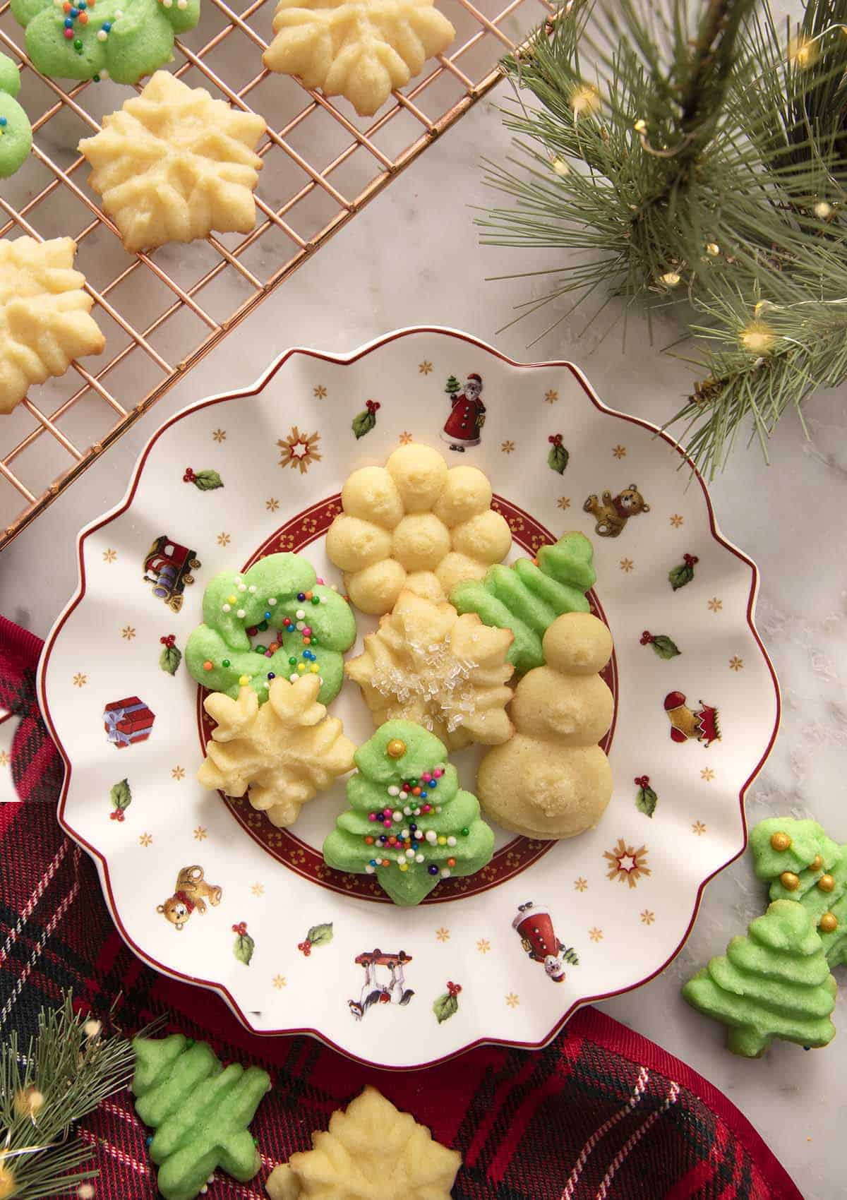 A white and red Christmas plate filled with green and white Christmas cookies.