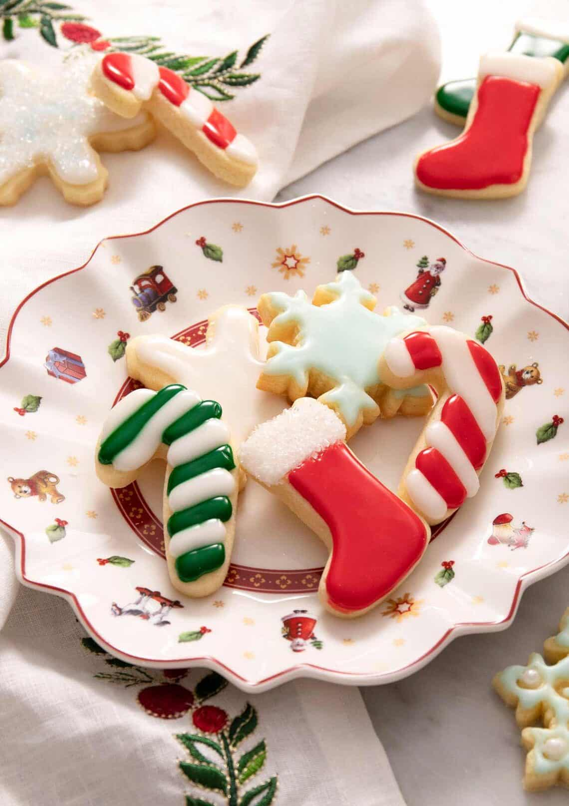 A side shot of Christmas sugar cookies with icing on a plate