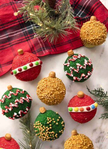 A group of cupcakes decorated as colorful Christmas ornaments.