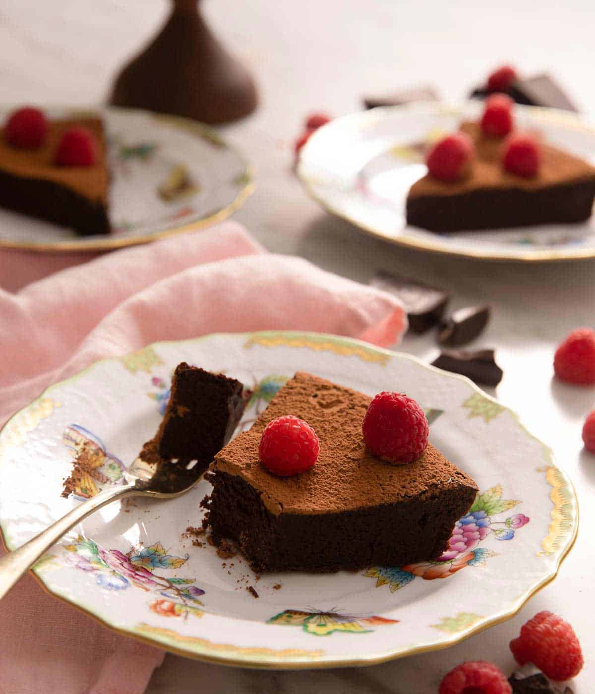 A slice of chocolate cake on a plate with a bite out