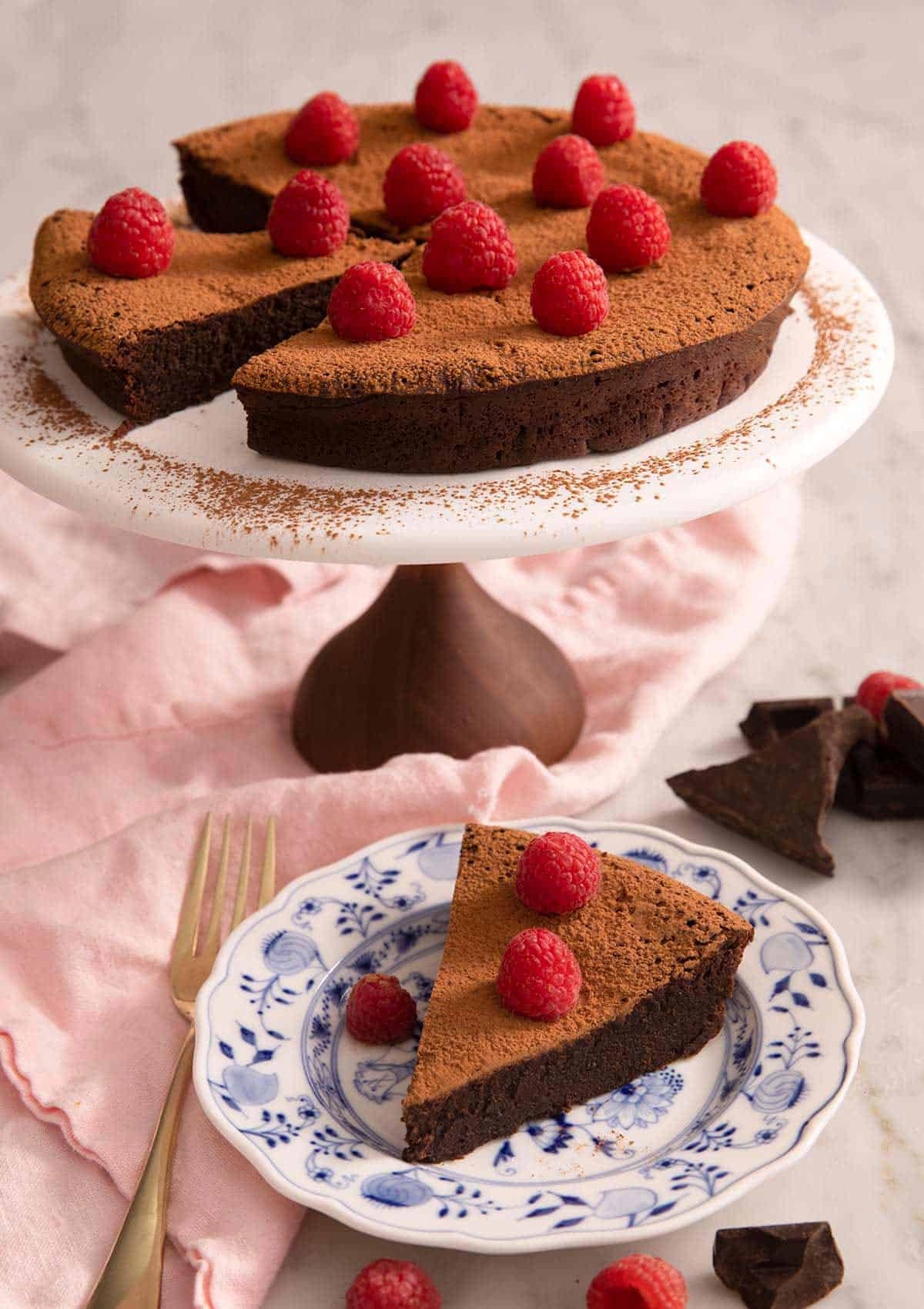 A flourless chocolate cake on a cake stand with a slice on a plate