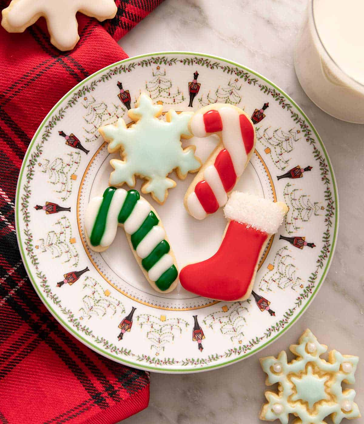 An overhead shot of a plate of Christmas sugar cookies with colored icing