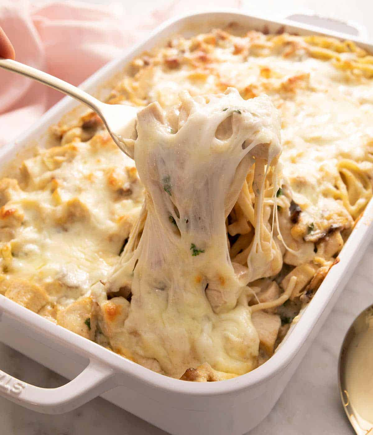 A spoon lifting up some chicken tetrazzini out of a baking dish with lots of melted cheese stretching