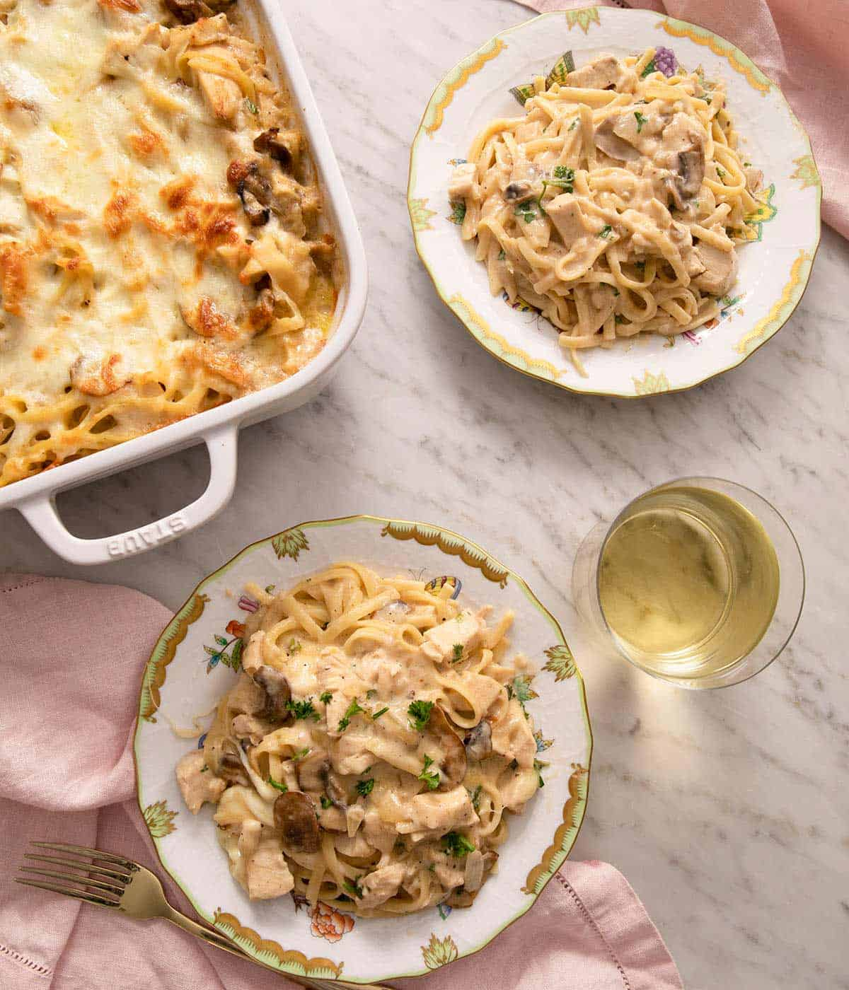 An overhead shot of chicken tetrazzini on two plate with a glass of wine
