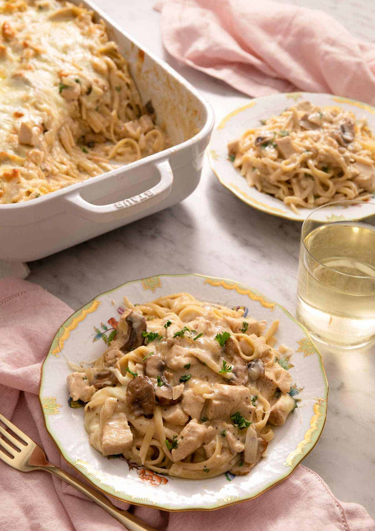 A side shot of chicken tetrazzini on a china plate with more plats and wine in the back ground