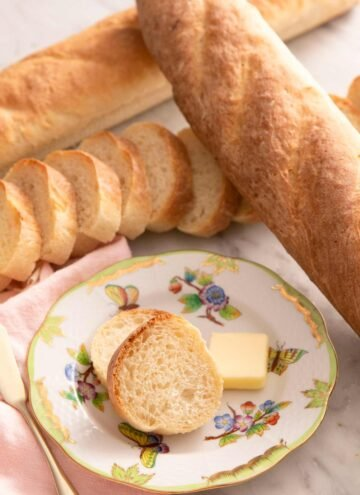 A close up of French bread on a plate with slices of butter