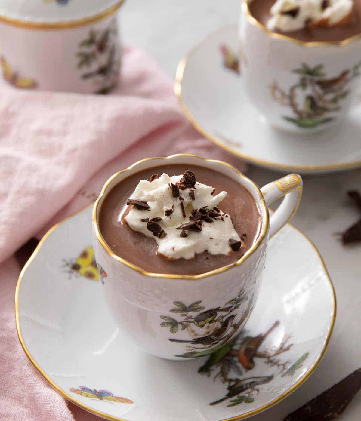 A side shot of a mug of hot chocolate topped with whipped cream