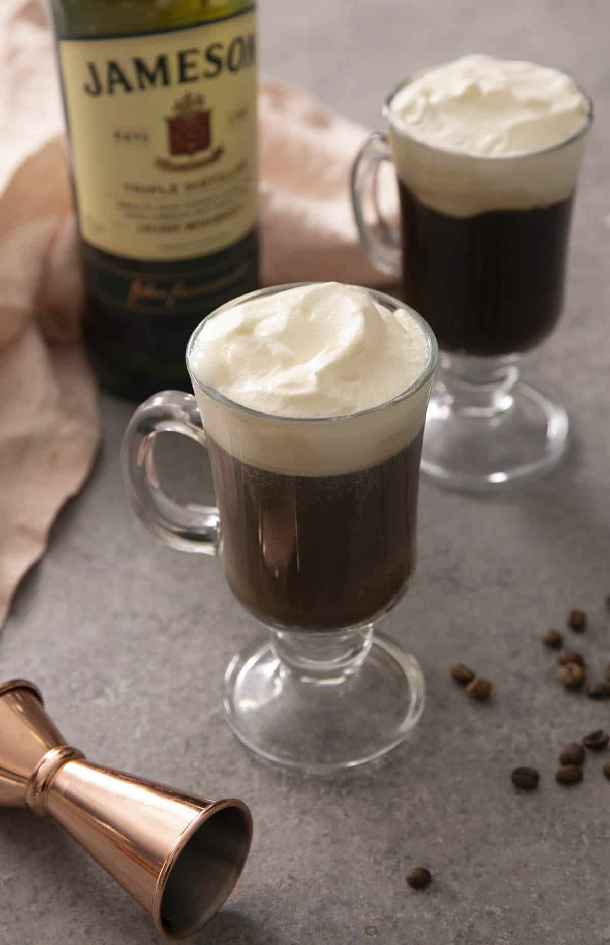 Two mugs on Irish coffee on a work surface with a bottle of whiskey in the background