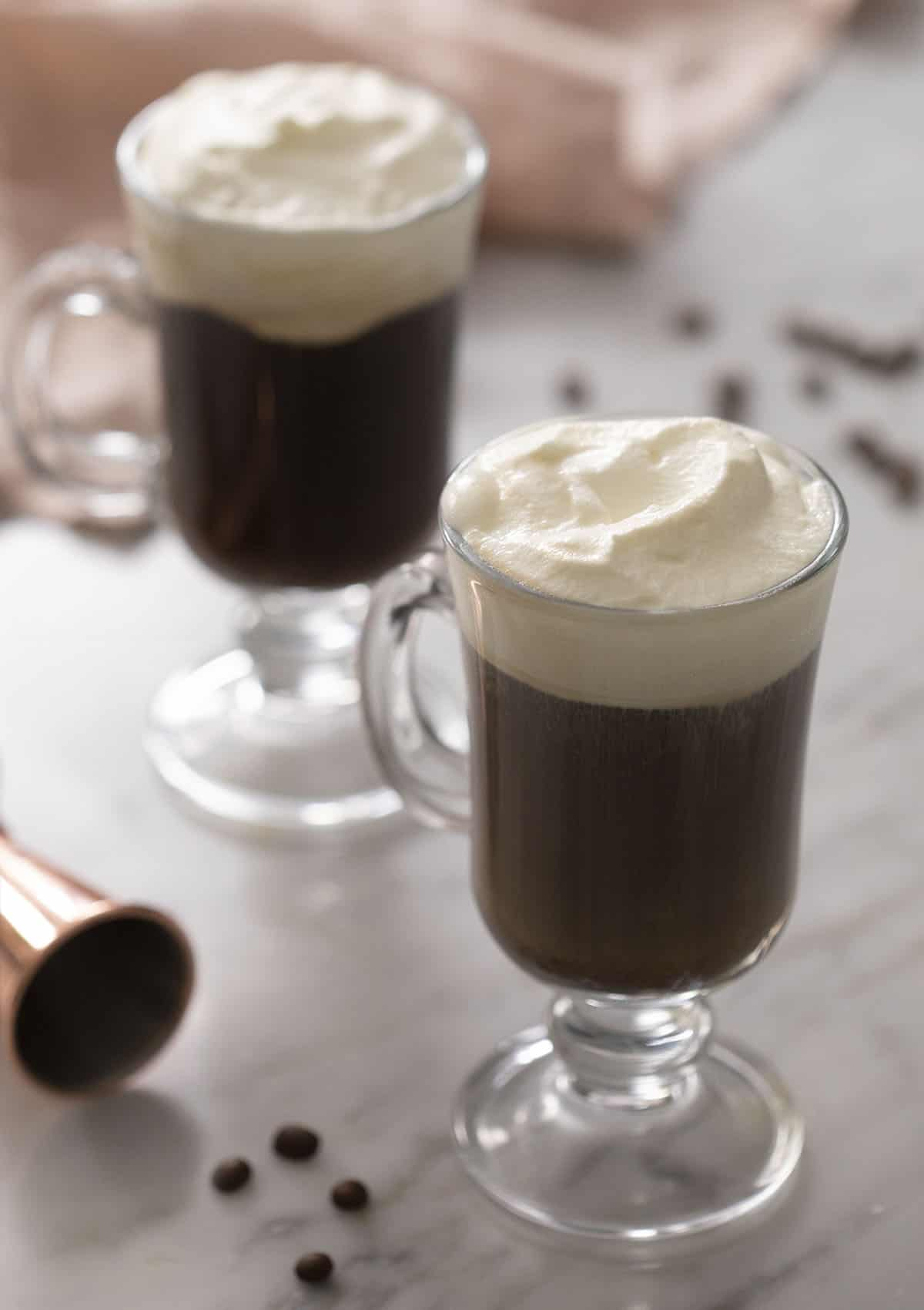 Two Irish coffees topped with whipped cream