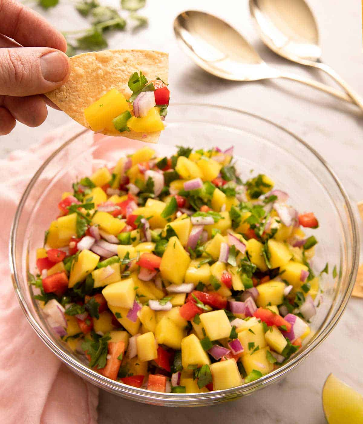 A chip picking up some mango salsa from a bowl