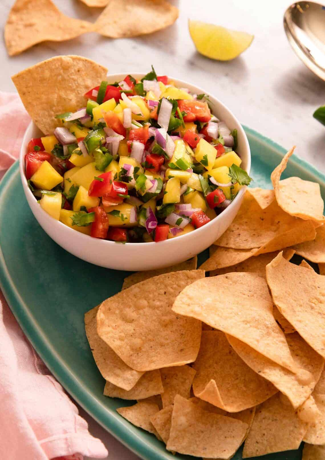 Mango salsa in a bowl with chips beside it