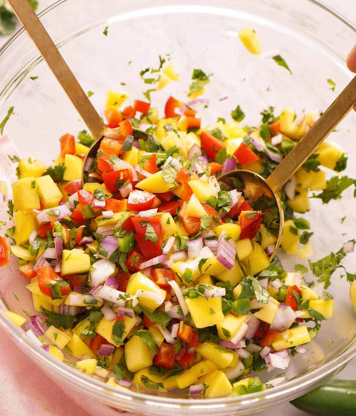 A close up of mango salsa in a large bowl with salad spoons