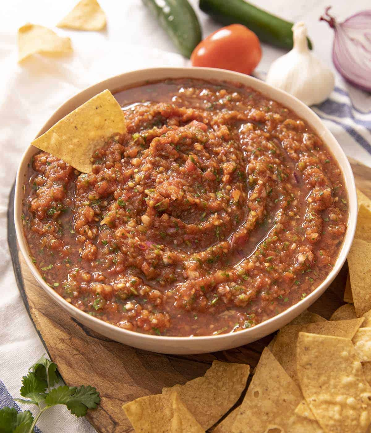 Salsa in a bowl with a tortilla chip at the side