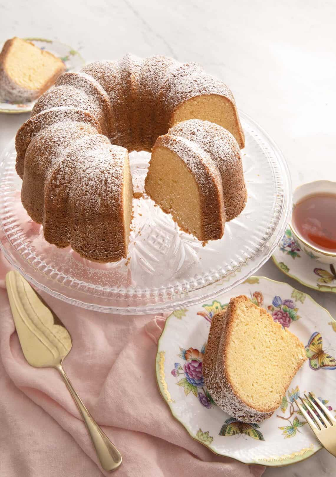 A sour cream pound cake on a cake stand with a slice on a plate