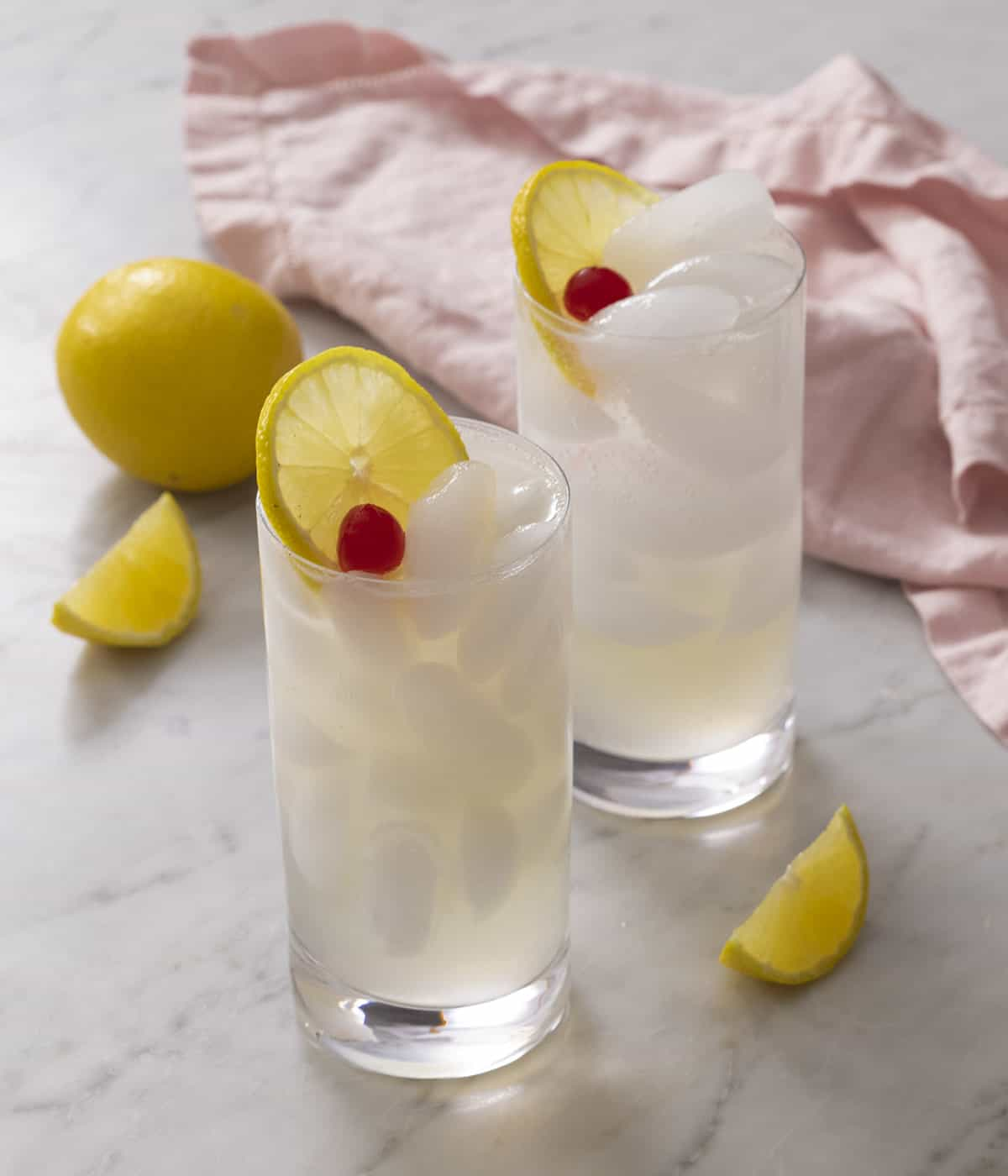 Two Tom Collins topped with cherries and lemon slices on a marble surface