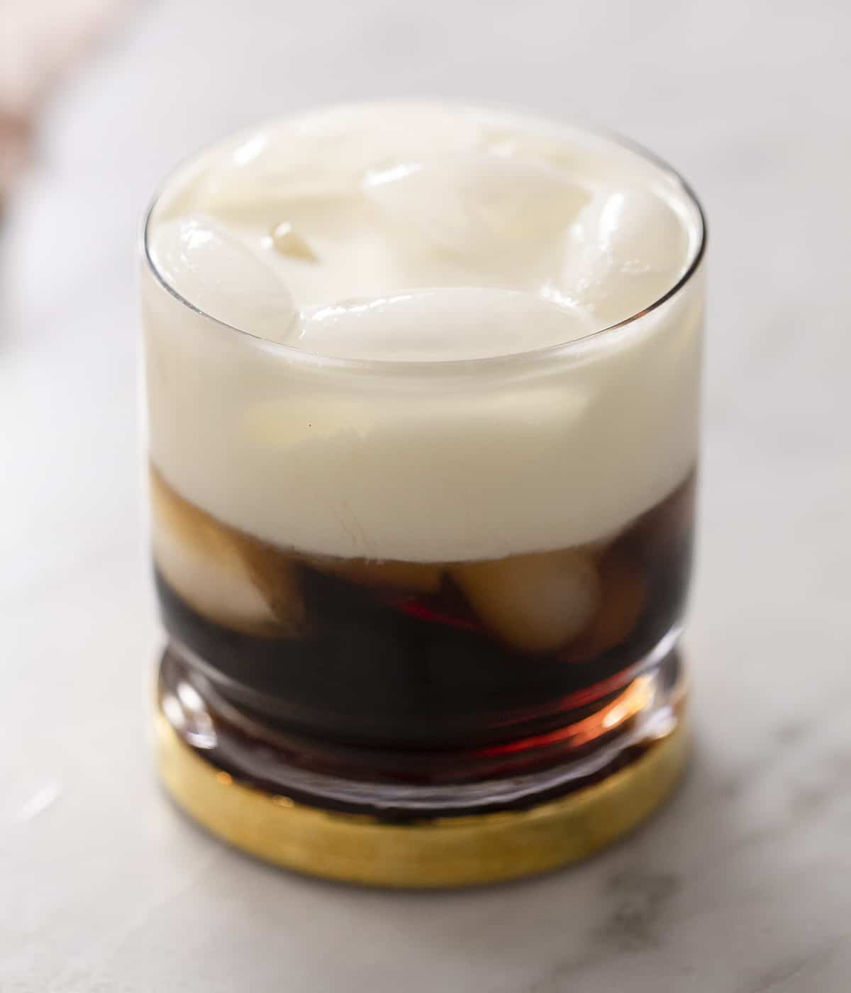 A close up of a White Russian cocktail in a glass filled with ice