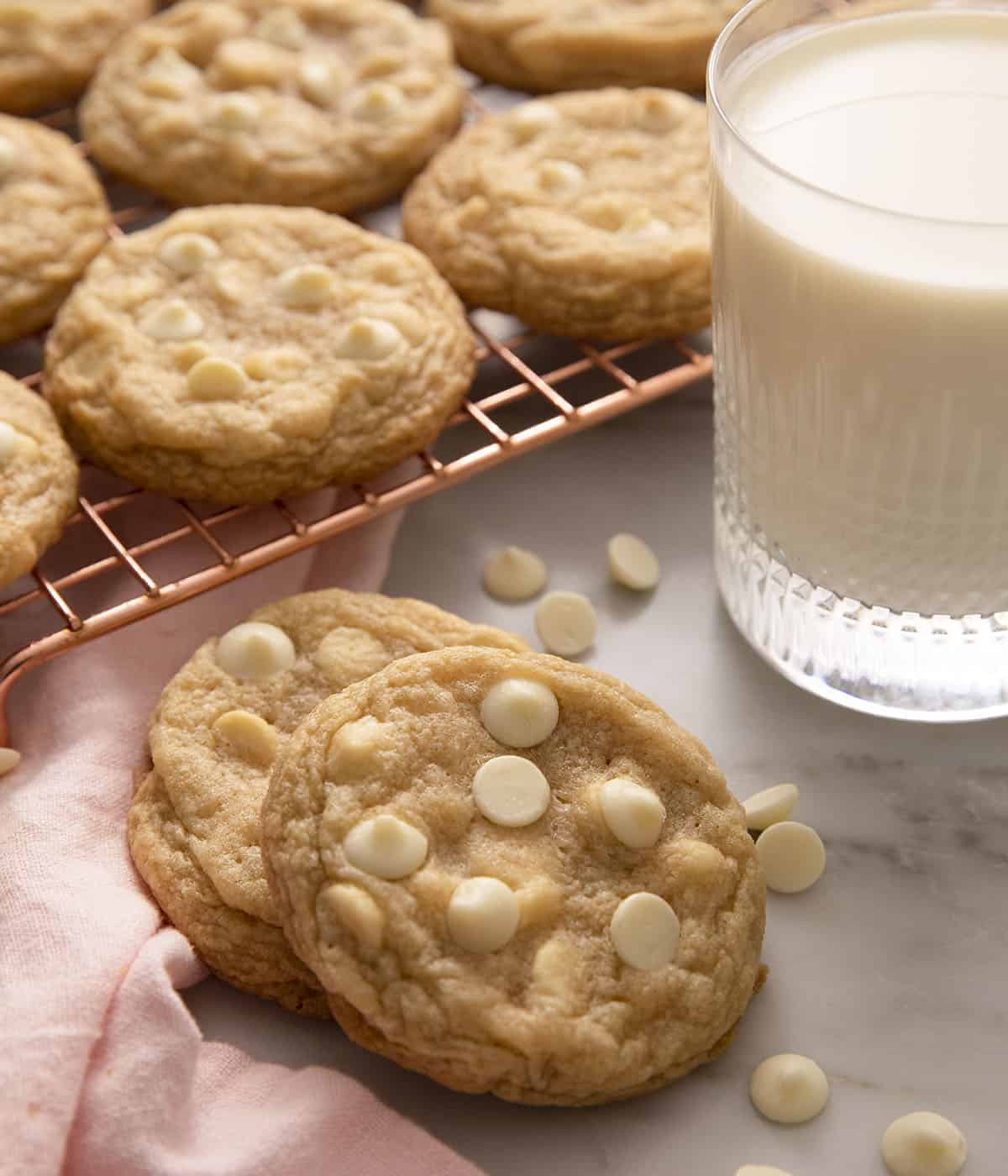 A close up of two cookies beside a glass of milk