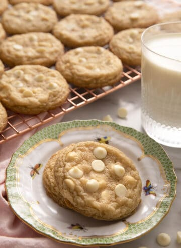 White chocolate chip cookies on a small plate and some on a cooling rack