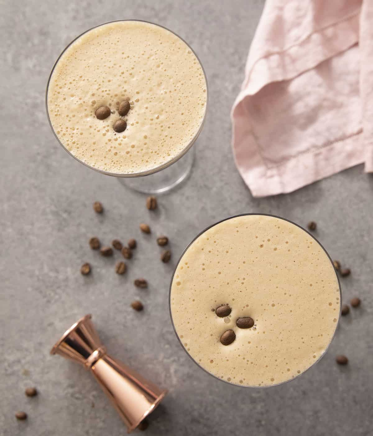 An overhead shot of two espresso martinis topped with coffee beans