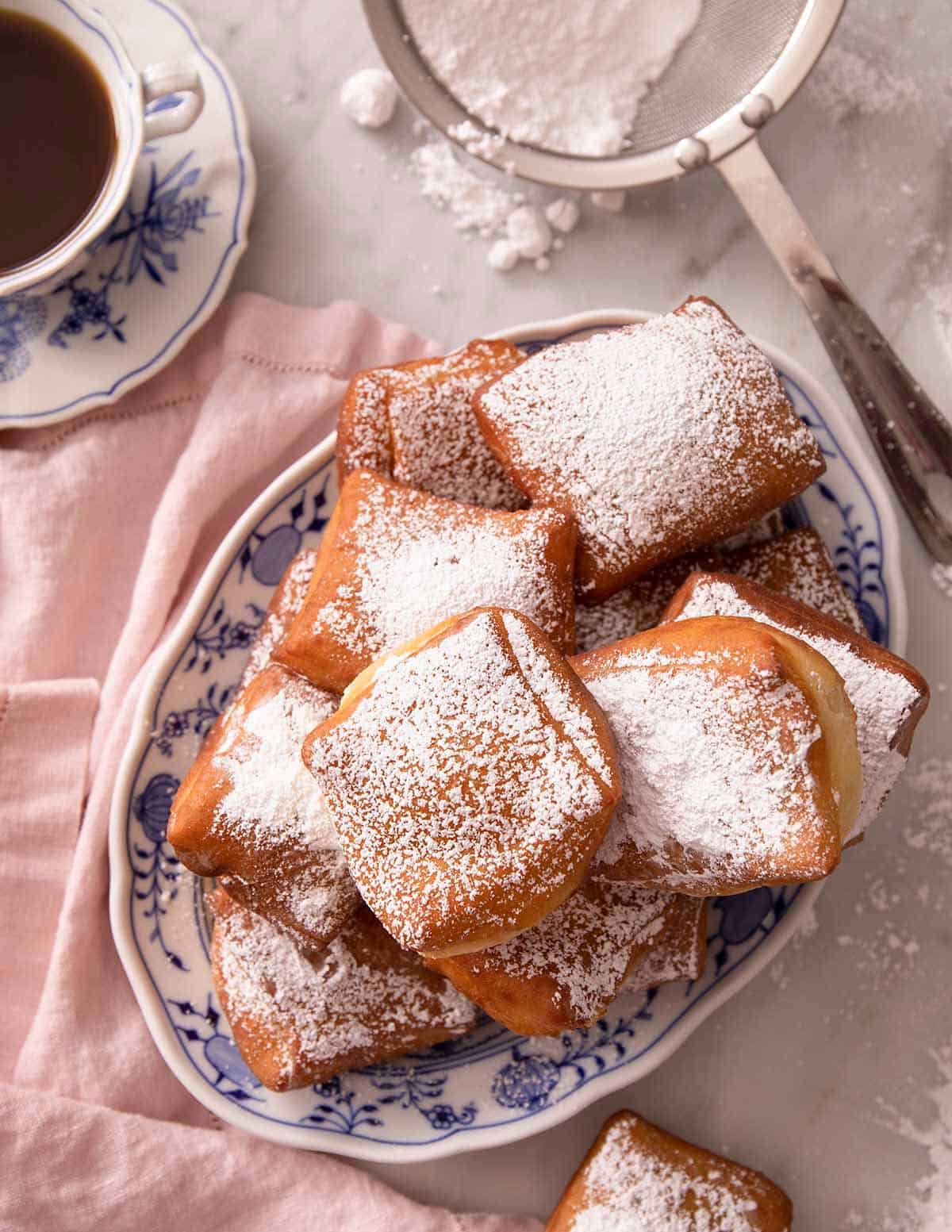 A pile of Beignets on a blue serving plate