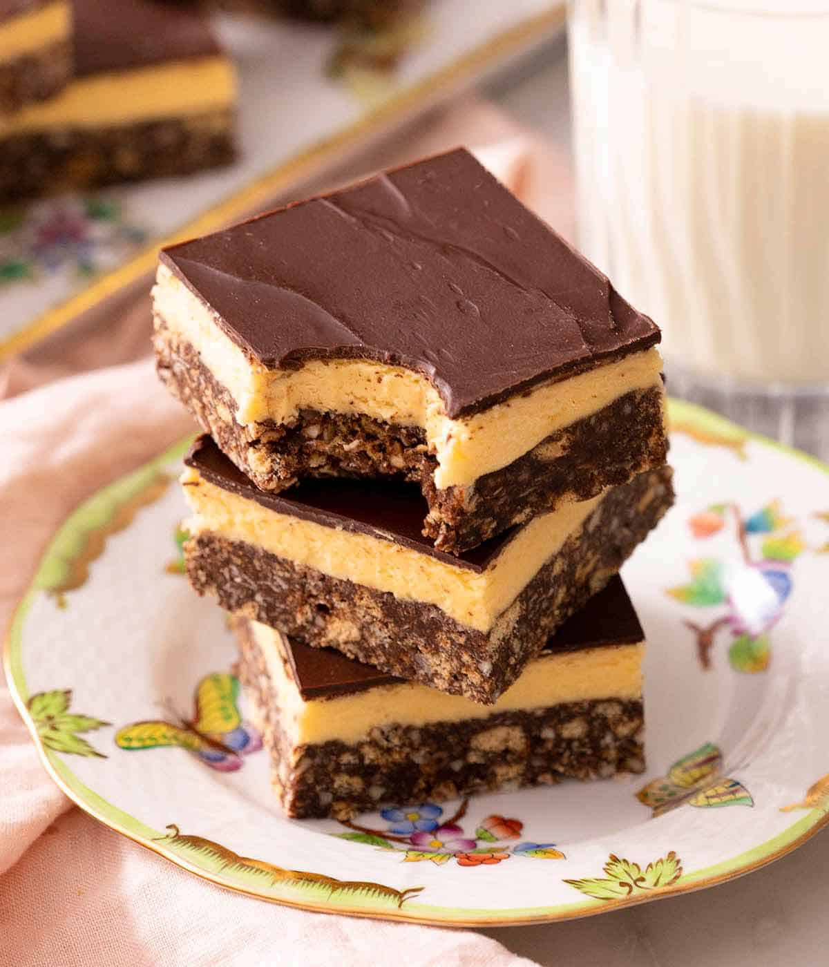 A stack of Nanaimo bars on a plate and one with a bite out