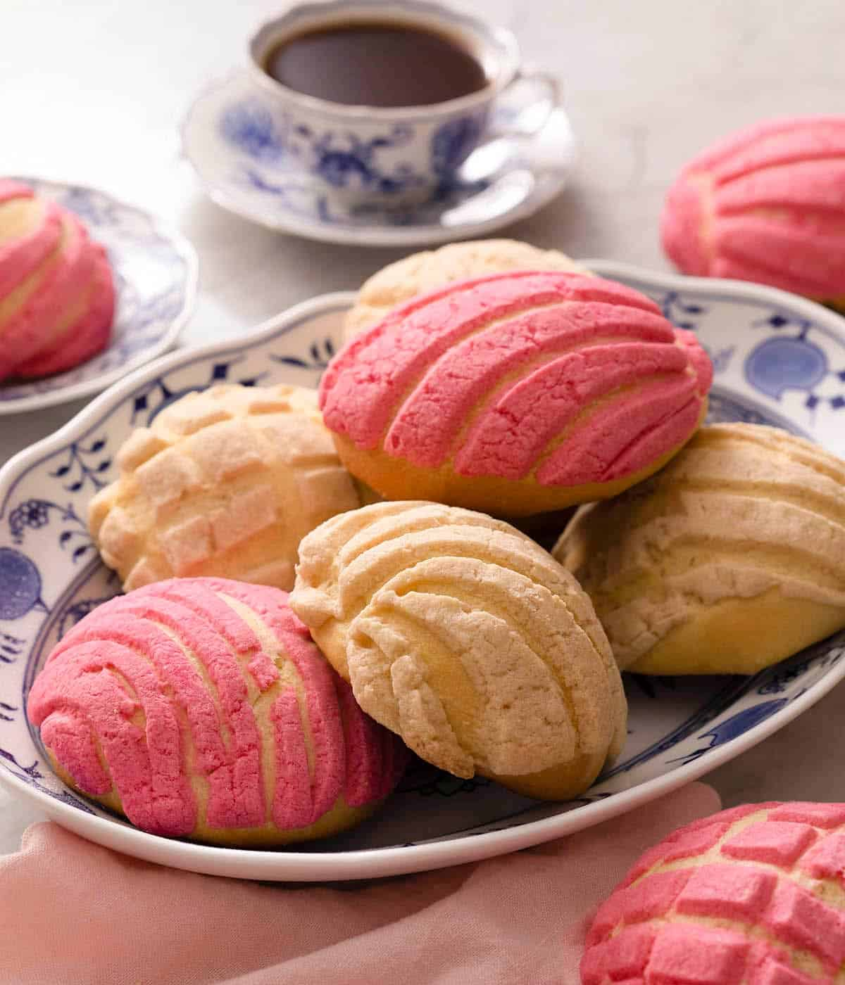 Pan Dulce on a blue serving plate with a cup of coffee in the background