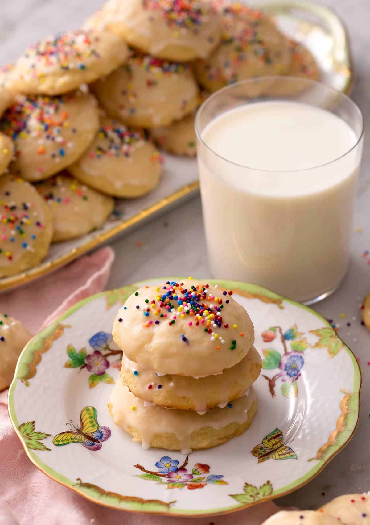 Ricotta cookies stacked on top of each other with a glass of milk in the background