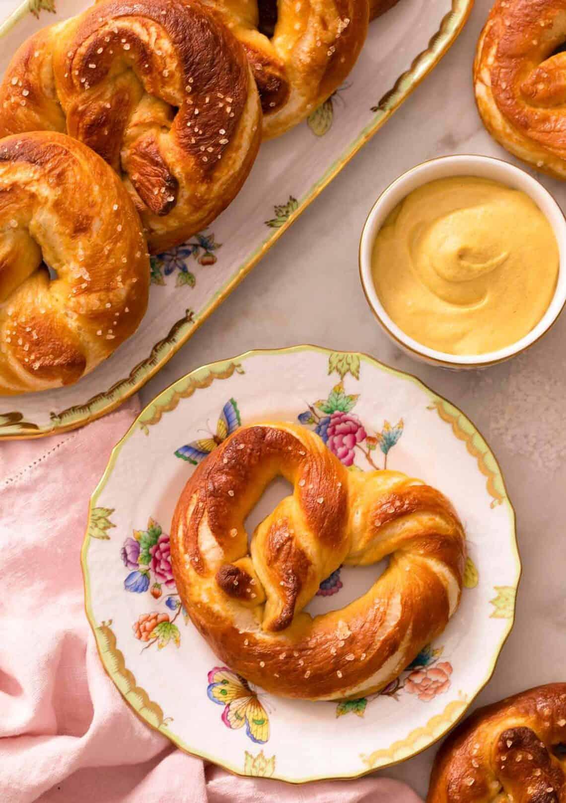 An overhead shot of a soft pretzel on a plate next to mustard