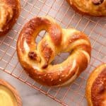 A close up of a soft pretzel on a cooling rack