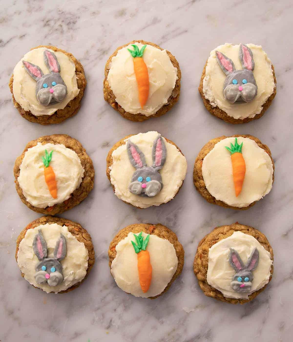Carrot cake cookies on a marble work surface frosted with carrots and bunnies