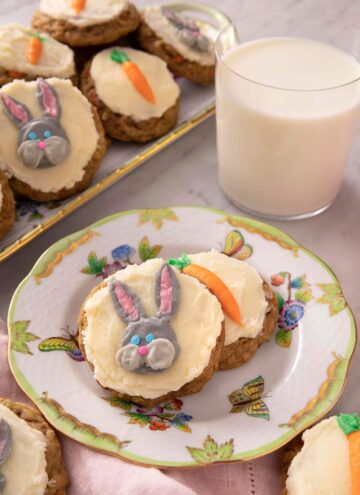 Carrot cake cookies on a plate with a glass of milk in the background