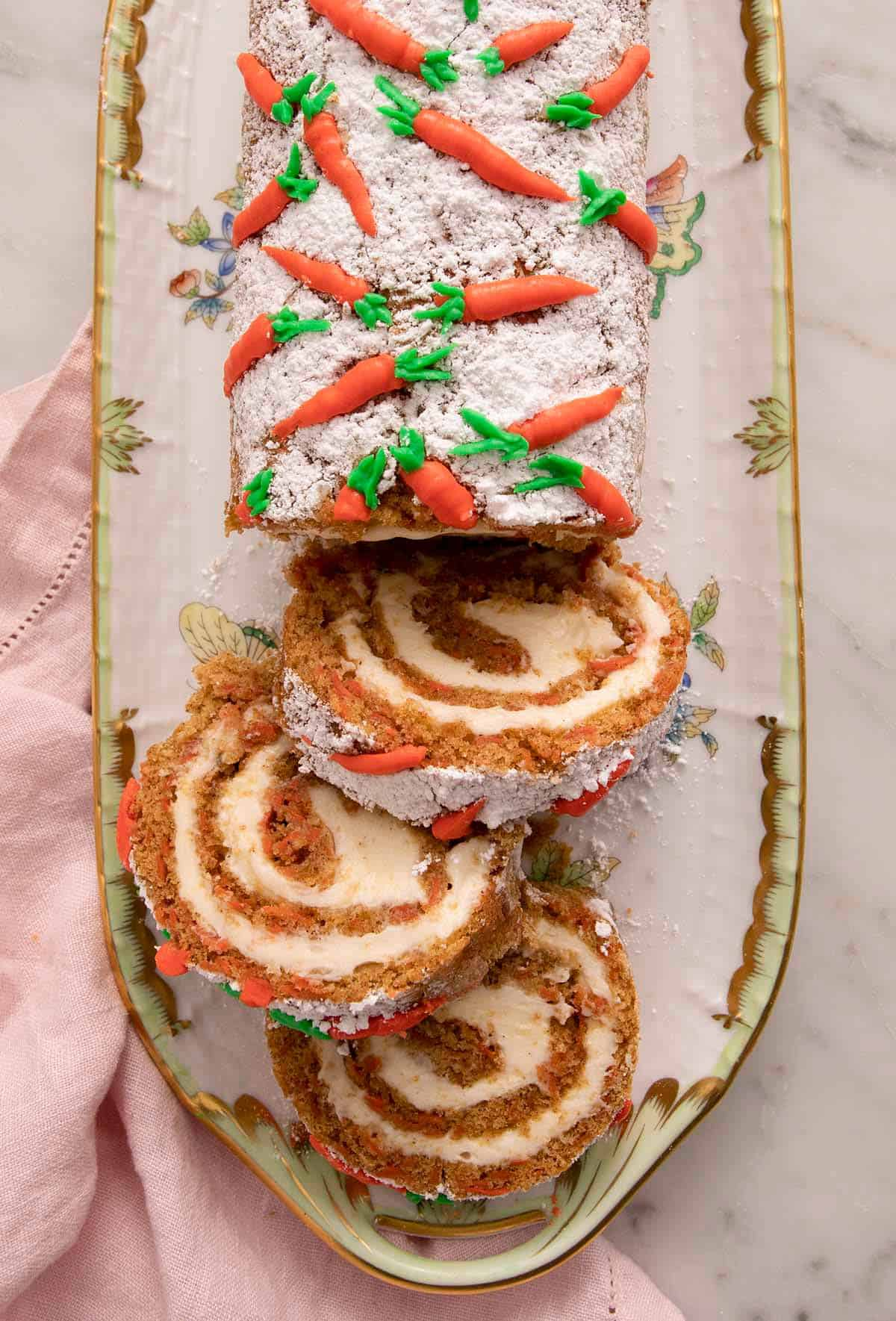 An overhead shot of a a carrot cake roll cut into slices